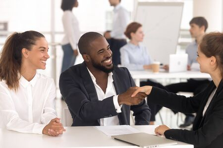 Excited multiethnic young couple shake hand with female banker get acquainted greeting at meeting, happy diverse married spouse handshake woman realtor closing successful deal. Cooperation concept 写真素材