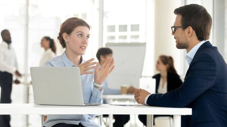 Konzentrierte Männer und Frauen sitzen am Schreibtisch und verhandeln mit Laptop über Ideen, verschiedene Kollegen reden über Brainstorming, verhandeln gemeinsam über Geschäftsprojekte. Kooperationskonzept Standard-Bild