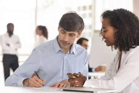 Concentrated male client put signature on contract closing deal at banker or broker office, smiling african American employer or recruiter watch man employee sign agreement. Hiring, employment concept