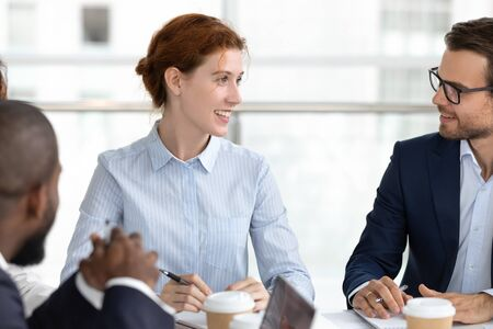 Smiling red-haired female employee talk share thoughts brainstorm with diverse colleagues at meeting in office, happy redhead woman speak discuss business idea or project with coworkers at briefing