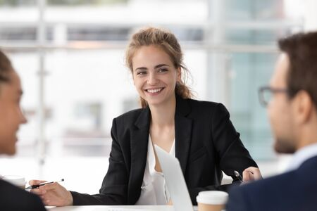 Smiling female employee listen to colleagues discussion talking sharing ideas at company briefing, happy millennial businesswoman sit at group meeting negotiating with coworkers in conference room Reklamní fotografie