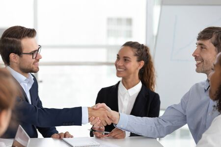 Smiling male employees handshake greeting introducing at company meeting in boardroom, excited business partners shake hands closing deal or get acquainted at office briefing. Partnership concept