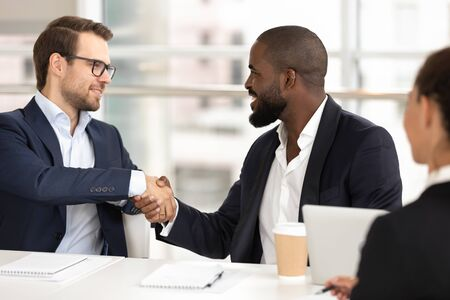 Smiling Caucasian millennial businessman handshake positive african American male business partner losing deal at meeting, diverse man employees shake hands get acquainted at office briefing Фото со стока - 137895518