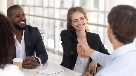 Excited millennial businesswoman handshake male business partner get acquainted at office meeting, smiling young female boss or ceo shake hand greeting with new employee at company briefing Stockfoto