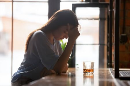Desperate millennial woman sit at wooden counter in bar having life relationships problems drinking alone, depressed female feel broken stressed suffer from serious alcoholism addiction