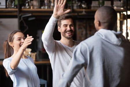 Fröhliche tausendjährige gemischtrassige Freunde umarmen sich in einer Bar, die bei einem freundlichen Treffen wieder vereint ist, überglückliche junge Leute umarmen einen willkommenen Kumpel auf einer Party im Café oder Restaurant. Freundschaftskonzept Standard-Bild