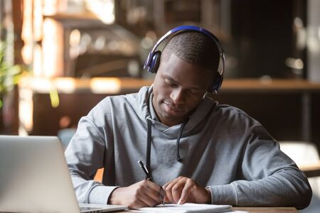 Focused african American male student wear modern wireless headphones busy studying at laptop, concentrated smart black guy in earphones write make notes in notebook use computer preparing for test
