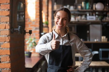 Smiling beautiful millennial waitress wearing black apron standing showing thumbs up recommending cafe, happy young restaurant staff looking at camera giving recommendation of good service place