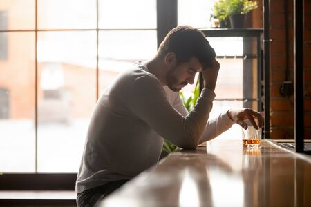 Depressed millennial man sitting alone at bar counter drinking strong alcohol thinking of relationships problems, stressed sad male feel despair pondering suffering from alcoholism. Addiction concept