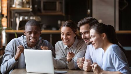 Excited diverse millennial friends gather in bar watching football match on laptop online, overjoyed hopeful fans young people hang out have fun in cafe cheering favorite sports team for win in game