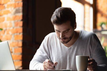 Estudiante masculino milenario concentrado sentado en una cafetería disfrutando de un café estudiando usando una computadora portátil, un hombre inteligente enfocado ocupado trabajando preparando un proyecto universitario en un café, tomar notas en un cuaderno, navegar por la web