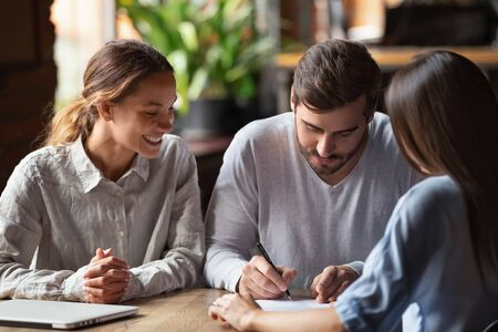 Excited young husband and wife sign contract taking loan or mortgage from female banking specialist, overjoyed millennial couple feel happy closing deal put signature on agreement meeting with realtor Zdjęcie Seryjne
