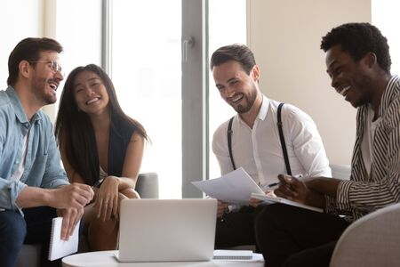 Overjoyed multiethnic millennial colleagues laugh discussing paperwork watching funny video on laptop at meeting, smiling diverse businesspeople have fun cooperating brainstorming at briefing together