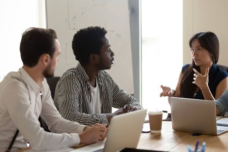 Diverse millennial businesspeople sit at desk talk brainstorm at team meeting in office, multiethnic young colleagues employees speak consider business ideas share thoughts at group briefing