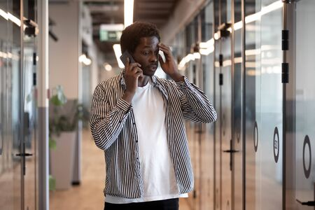 Serious millennial african American male employee stand in modern office hallway talking on cellphone, thoughtful biracial man worker busy speaking chatting using gadget having smartphone call Zdjęcie Seryjne