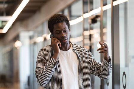 African American millennial male hold smartphone having online business call or conversation with client, biracial man worker businessman solve issues over cell, talking using cellphone gadget Zdjęcie Seryjne