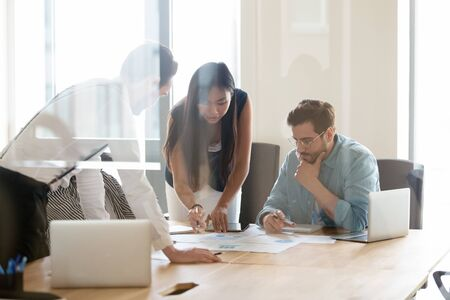 Thoughtful millennial multiethnic businesspeople brainstorm consider paperwork statistics at office meeting, diverse colleagues talk discuss paper report share business ideas at briefing