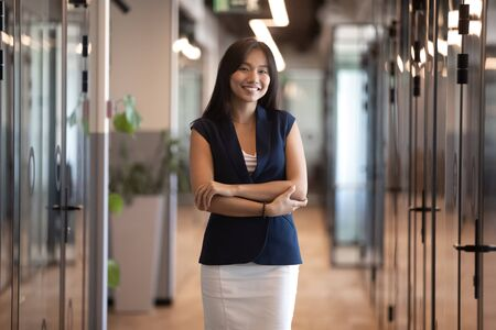 Portrait of smiling Asian millennial businesswoman stand in modern office hallway posing, happy confident young female employee or boss look at camera make picture in business workspace