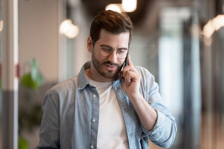 Close up of millennial businessman hold smartphone talking chatting using wireless connection in office, young male employee worker in glasses have pleasant cellphone call, use modern technology cell Zdjęcie Seryjne
