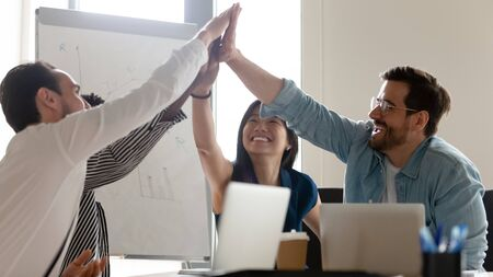 Overjoyed millennial multiracial employees give high five involved in teambuilding activity at briefing in office, excited diverse colleagues join hands celebrating shared success at meeting