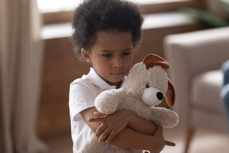 Close up headshot cute adorable sad african american little boy embracing soft toy, hurt upset offended sensitive kid looking aside feels lonely, family conflicts, parents divorce concept. Stok Fotoğraf