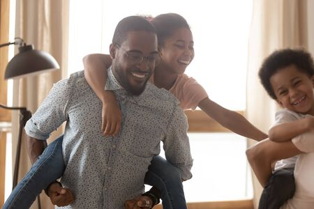 Close up funny daughter sitting on happy african american fathers back, tickling cute smaller brother, smiling multiracial family having fun in living room, active leisure time spending concept.