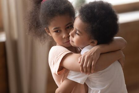 Close up sad elder african american sister hugging, holding, cuddling smaller upset offended cute brother, feeling sorry, warm friendly peaceful relationship between children, adoption concept.