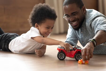 Close up happy african american man in eyeglasses and cute curly kid son playing with plastic auto cars toys, having fun together, spending active weekend, lying on heated floor at living room. 스톡 콘텐츠