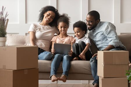 Happy smiling african american family of four sitting together on couch in modern living room, cute daughter and son holding computer, watching funny videos after unpacking and moving in new house.