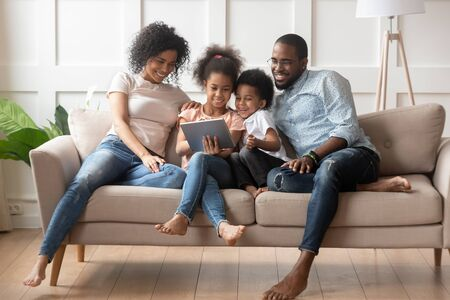Happy parents with smiling kids sitting on sofa, using tablet looking at screen, watching cartoons online, funny videos together, little girl showing family photos on gadget, making order, ecommerce