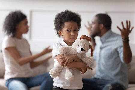 Stressed kid son feeling lonely, upset little african american boy holding embracing soft toy, suffering from parents quarrel, family conflicts, negative emotions, divorce or break up concept.