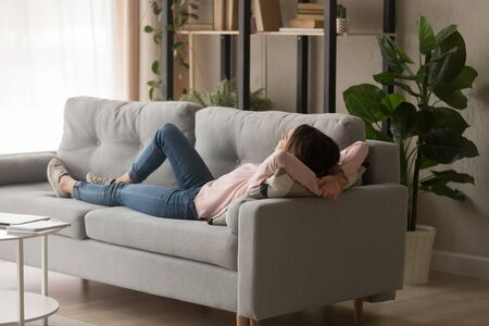 Young woman in casual clothes crossing hands behind head, sleeping on couch in modern cozy living room. Millennial lady relaxing, daydreaming, having rest at home on weekend. 版權商用圖片