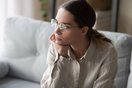 Upset young mixed race woman in eyeglasses sitting on couch in living room, holding head in hand, looking outside, thinking over problems, making difficult decision, feeling tired, exhausted.