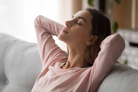 Close up side view young attractive woman face. Millennial lady leaning on cozy couch with crossed hands behind head, closed eyes having a break, resting, relaxing, daydreaming, no stress concept.