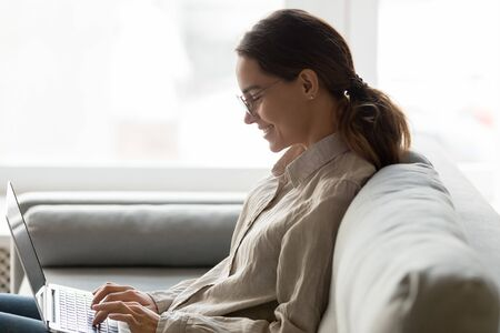 Side view of young happy mixed race woman in eyeglasses typing message in computer, shopping, dating online, chatting with friends. Successful self-employed millennial lady working remotely at home. Stock fotó