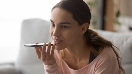 Close up cropped image happy millennial woman holding mobile phone, recording audio message, using virtual assistant or voice mic recognition software, chatting with friends in popular messenger.