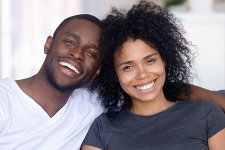 Portrait of happy young African American couple hug sitting on couch at home, smiling black husband and wife look at camera, embrace relaxing together on sofa. Healthy relationships concept Banco de Imagens - 138164913