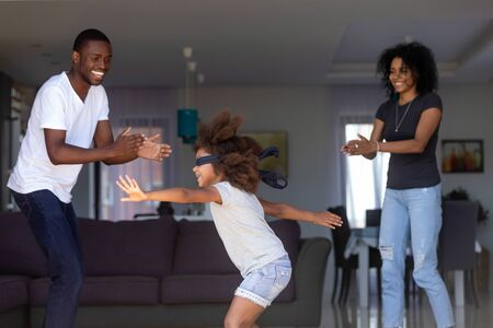 Funny little African American girl with blindfolded eyes play hide and seek with young parents at home, black family of three have fun enjoying childish game, laughing entertaining together on weekend