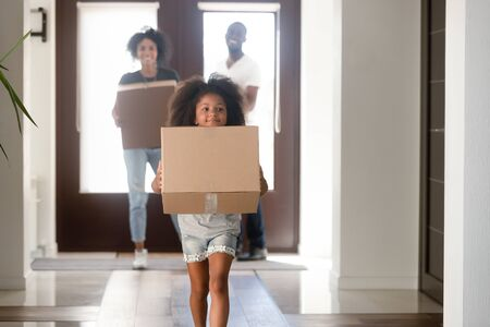 Happy small African American girl holding cardboard box run into new house, young black family moving into bought apartment, excited daughter carry personal belongings to home. Relocation concept