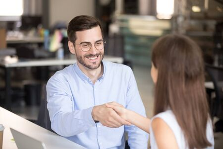 Excited manager in glasses shake hand of young female intern congratulating with job offering, happy male coach or employee handshake woman trainee greeting with employment in company