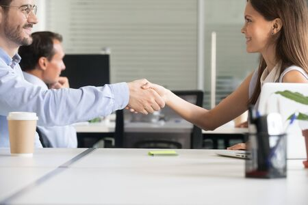 Smiling businesspeople shake hands closing deal after successful negotiations in office, happy millennial female employer handshake male business partner, greeting with employment or partnership
