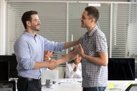 Smiling male boss or CEO handshake excited intern or newcomer congratulating with employment, employer shake hand of employee greeting with job promotion or work success. Reward concept Фото со стока - 137955839