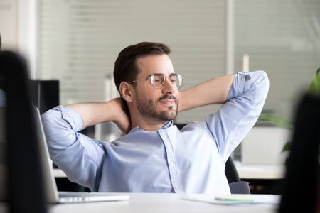 Dreamy male employee relax in chair hands over head looking distance thinking of future achievement, thoughtful man worker take break from work resting at workplace making plans or predictions