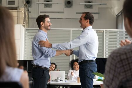Boss or CEO shake hand of male employee congratulating with job promotion at work, company employer handshake newcomer or newbie greeting with employment or hiring. Recruitment concept Фото со стока