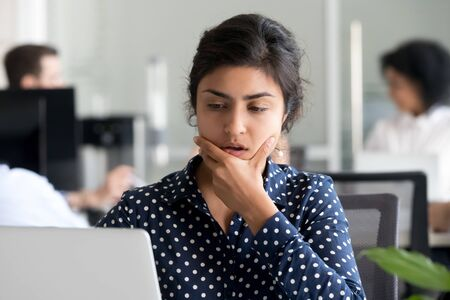 Pensive millennial indian employee work at laptop in coworking space think over problem solution, thoughtful young female worker use computer, consider startup project, making decision