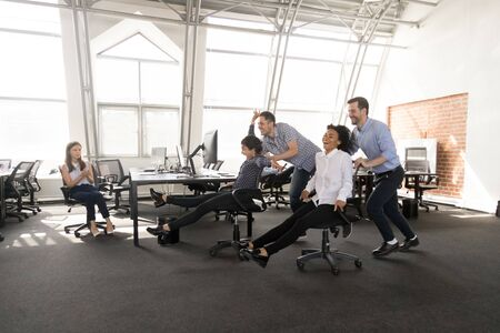 Excited millennial diverse workers have fun in office racing on chairs together, happy multiracial employees engaged in teambuilding activity, laughing entertaining during work break