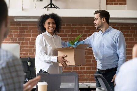 Male millennial boss speak introducing excited African American new worker to company team, happy black young female newcomer with belongings box on first work day get acquainted with colleagues