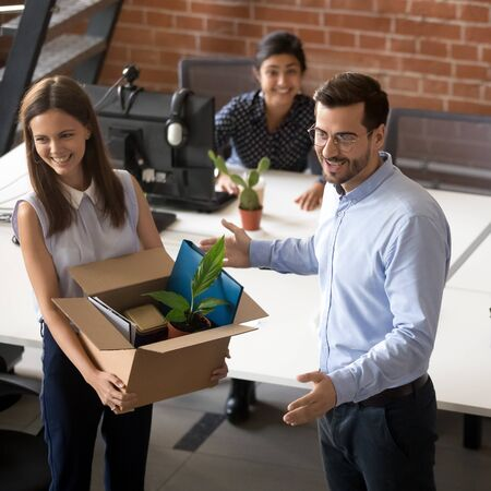 Smiling male CEO or boss introduce excited millennial woman employee to office colleagues, happy newcomer hold belongings box get acquainted with coworkers on first work day, welcome in team