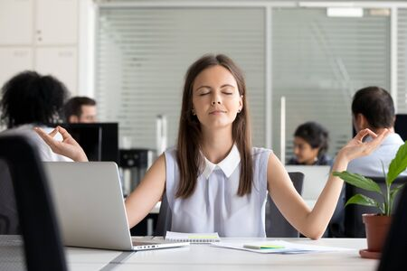 Calm millennial female employee meditate in shared office relieving negative emotions, young woman worker practice yoga with eyes closed at workplace, distract from bad thoughts. Stress free concept Foto de archivo - 137960747