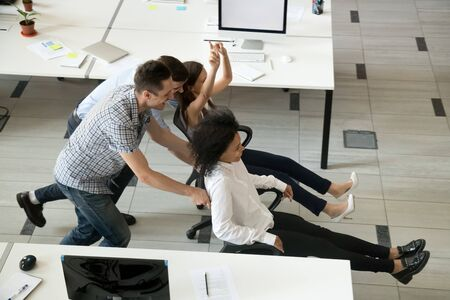 Excited diverse employees have fun in office riding on chairs during work break, multiracial millennial colleagues laugh entertaining at workplace, playing race game or involved in teambuilding